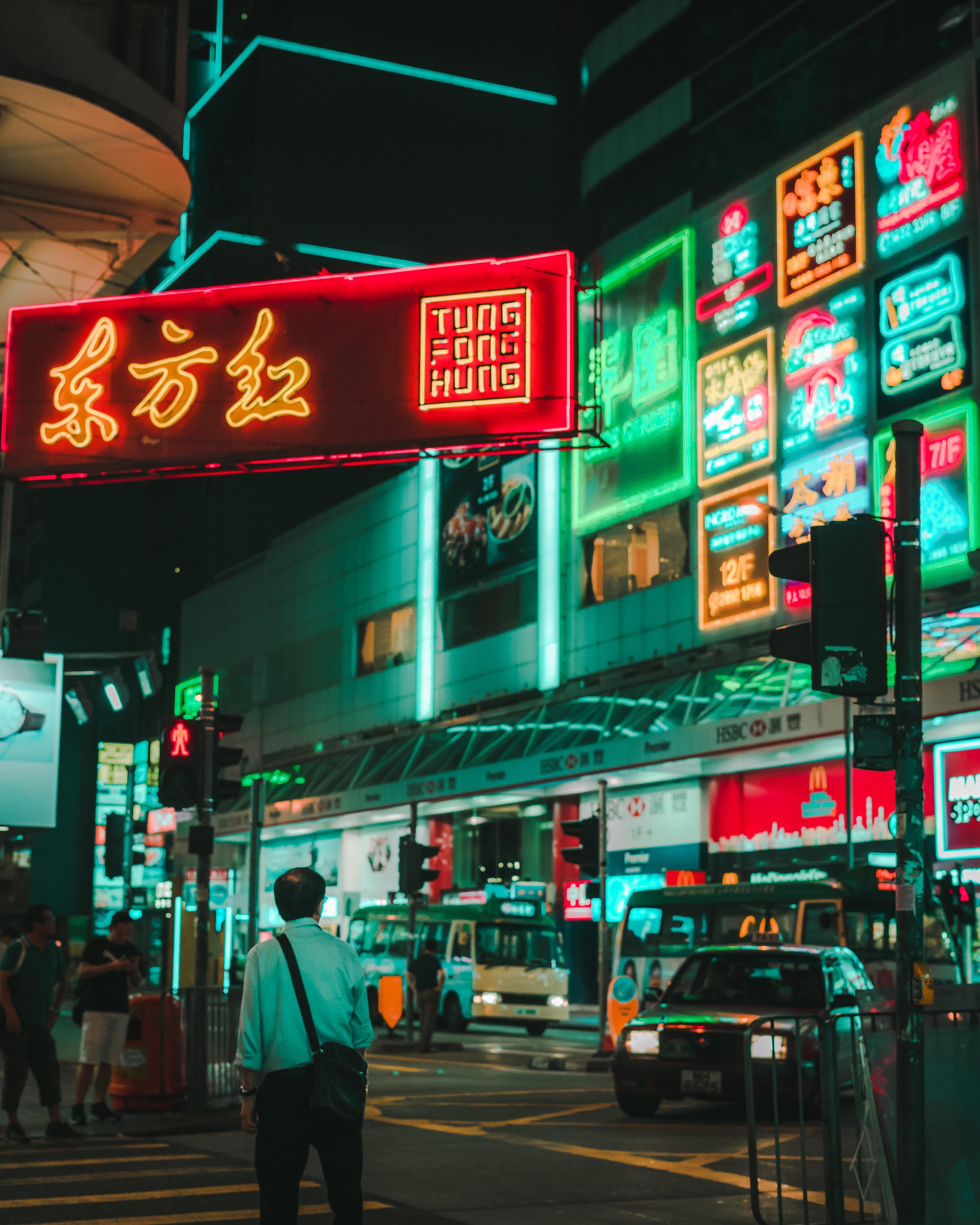 man walking on street under tung fong hung signage