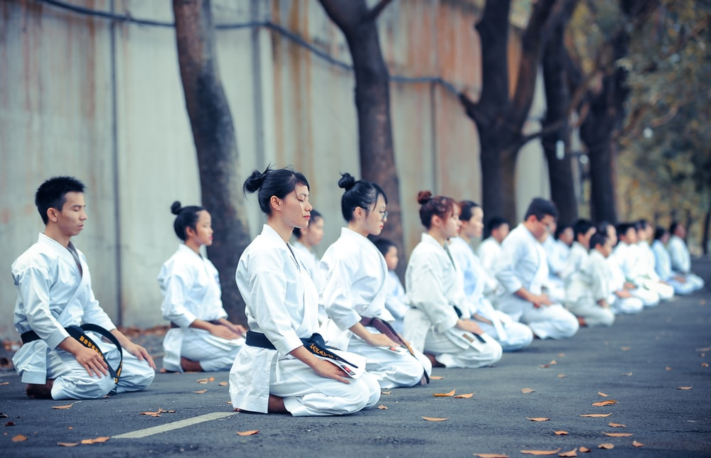 group of martial artists sitting on the grounds