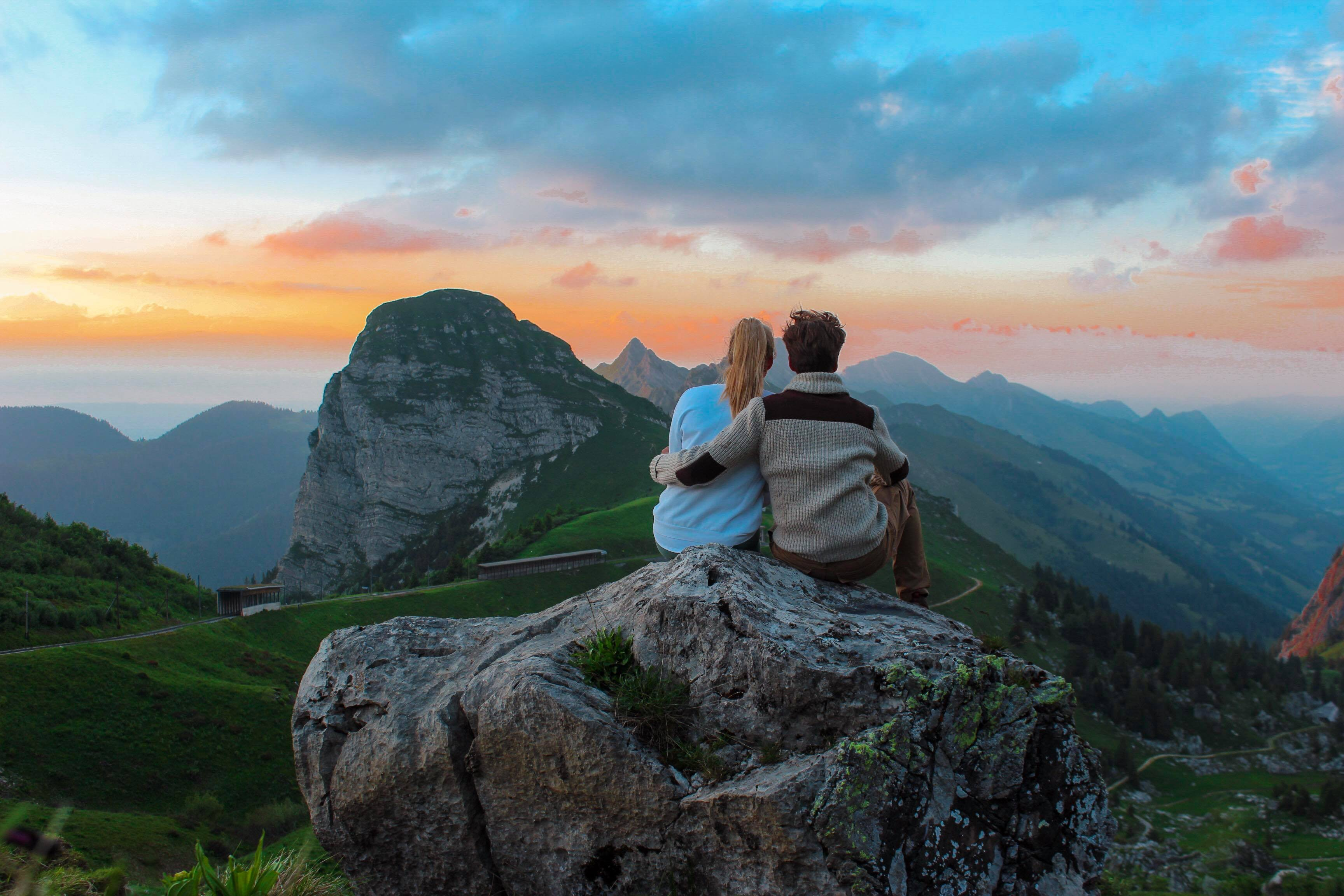 couple sitting on rock facing mountain view