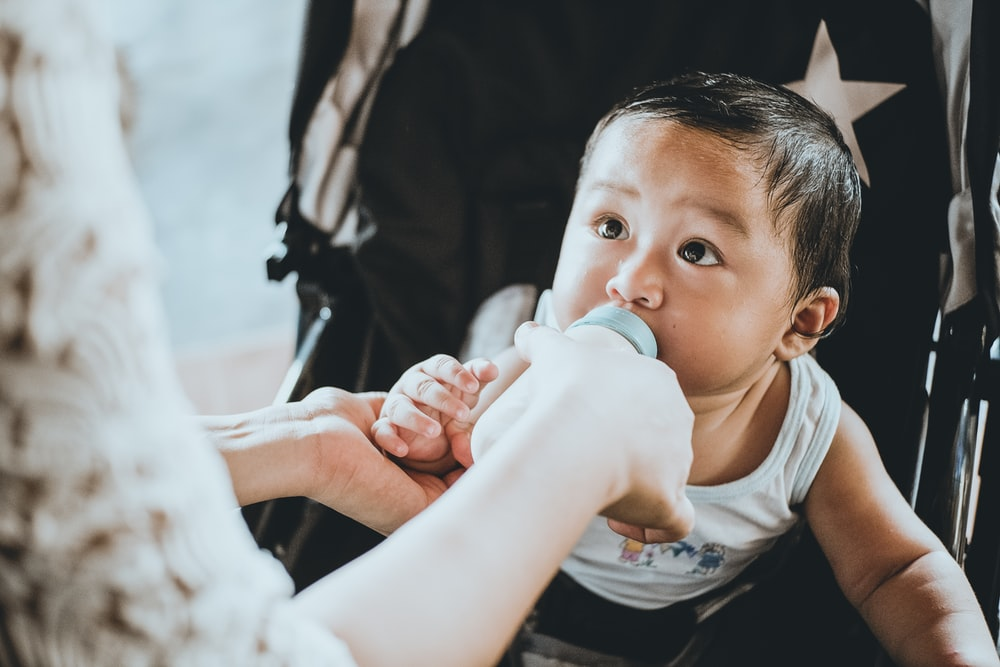 person feeding baby from feeding bottle