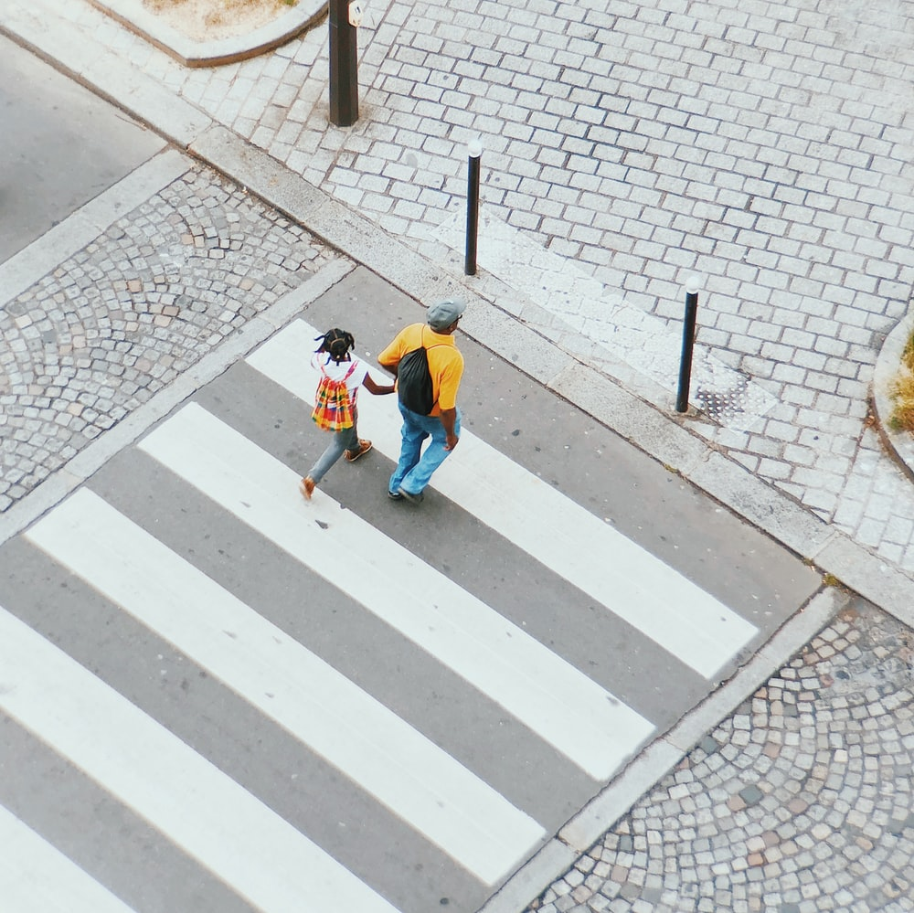 man and girl crossing on pedestrian lane
