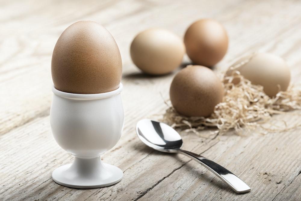 white ceramic egg holding near spoon