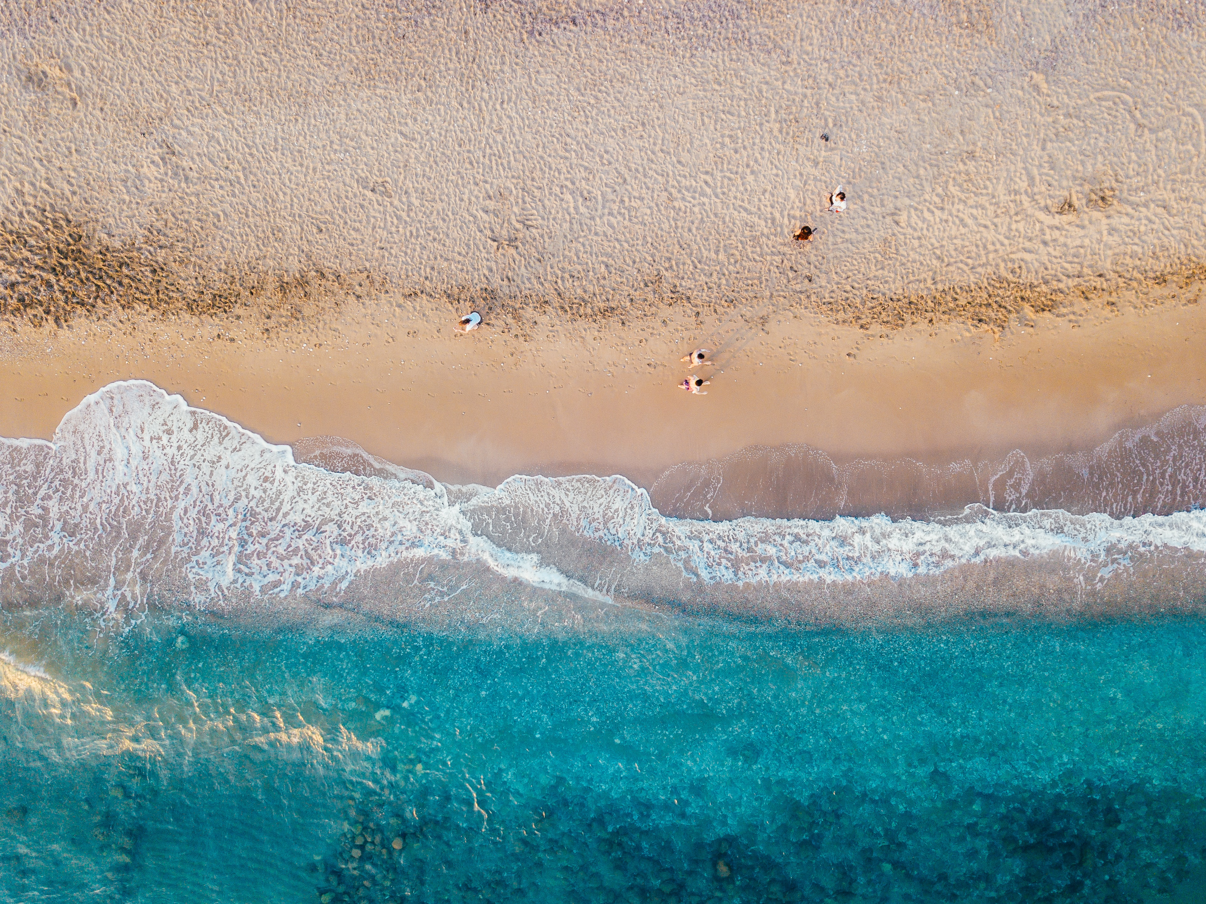 aerial photo of people standing on sand beach near teal sea wave at daytime