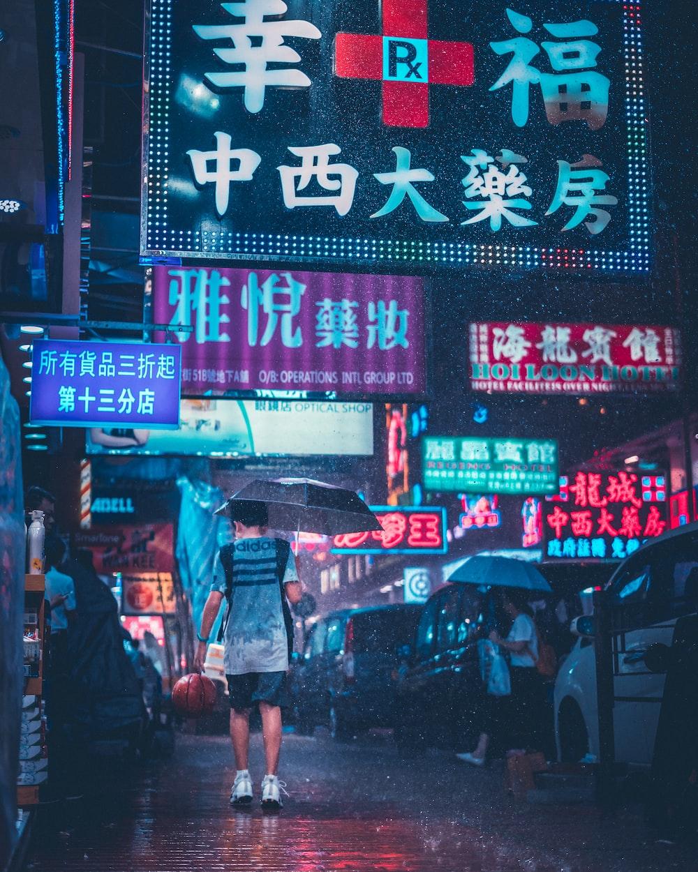 man in adidas shirt with umbrella walking in street under the rain
