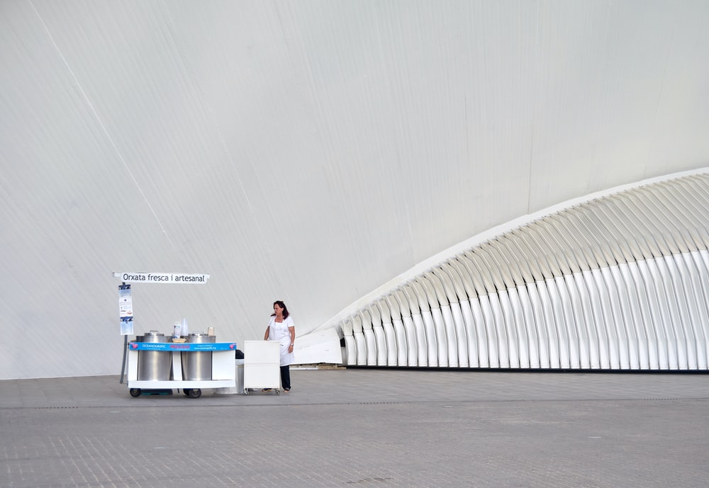 woman wearing white dress and black pants near stall