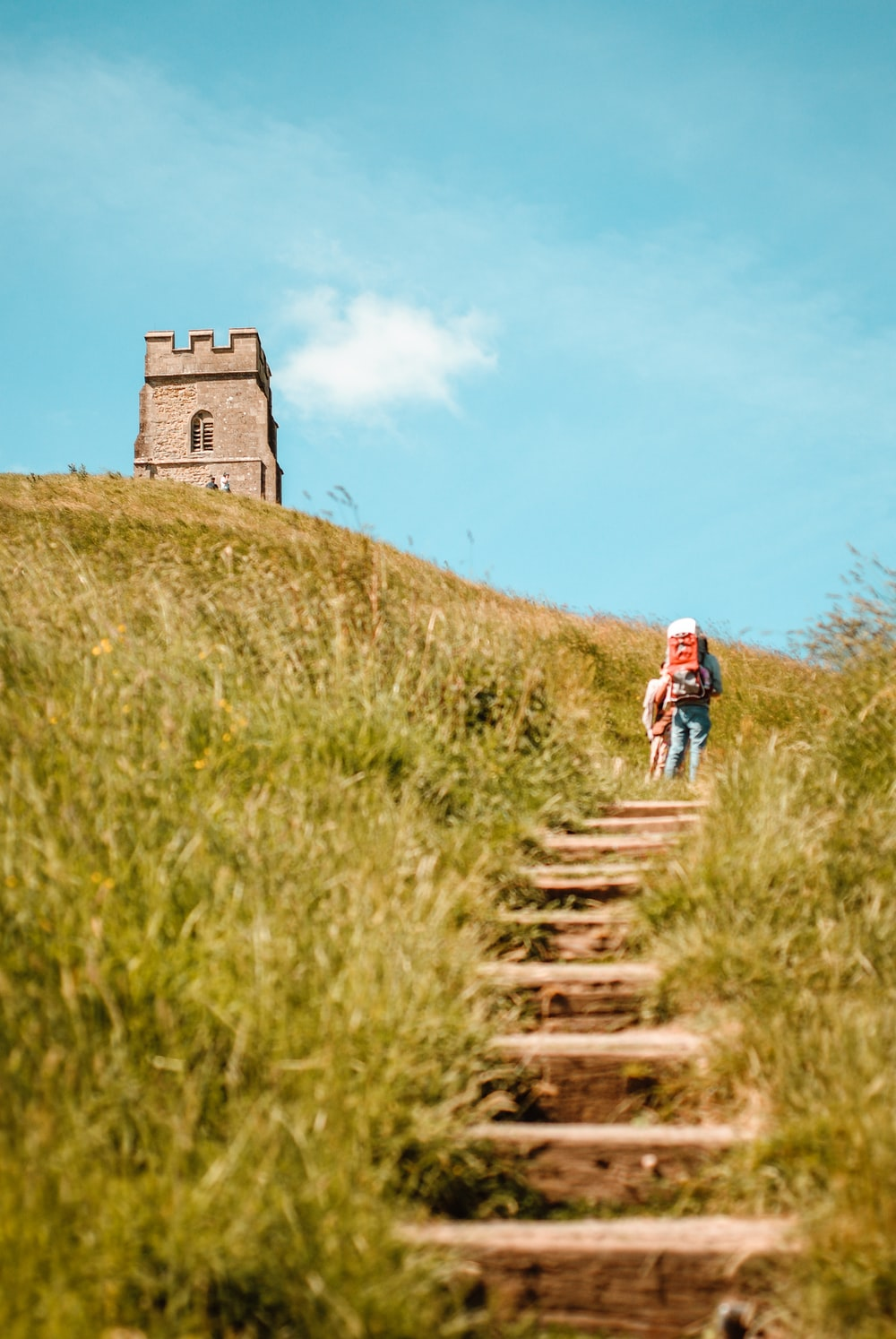 two person walks on hills near concrete stucture