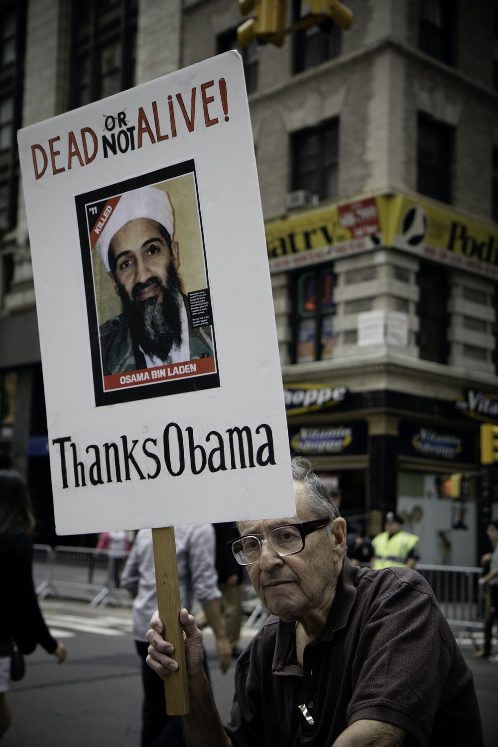 man sitting holding Dead Not Alive! Thanks Obama placard