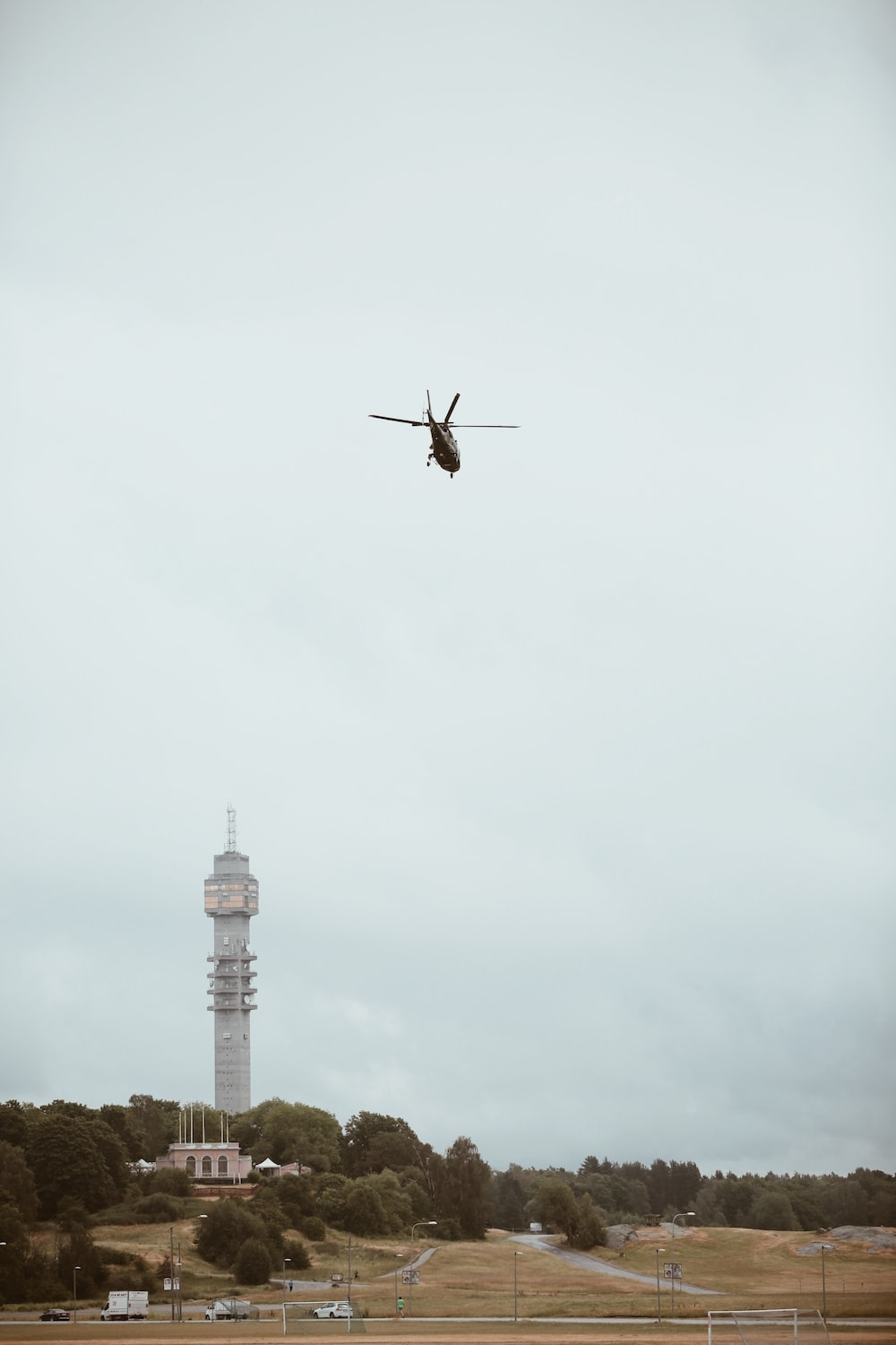 low-angle photography of black helicopter over gray concrete tower during daytime
