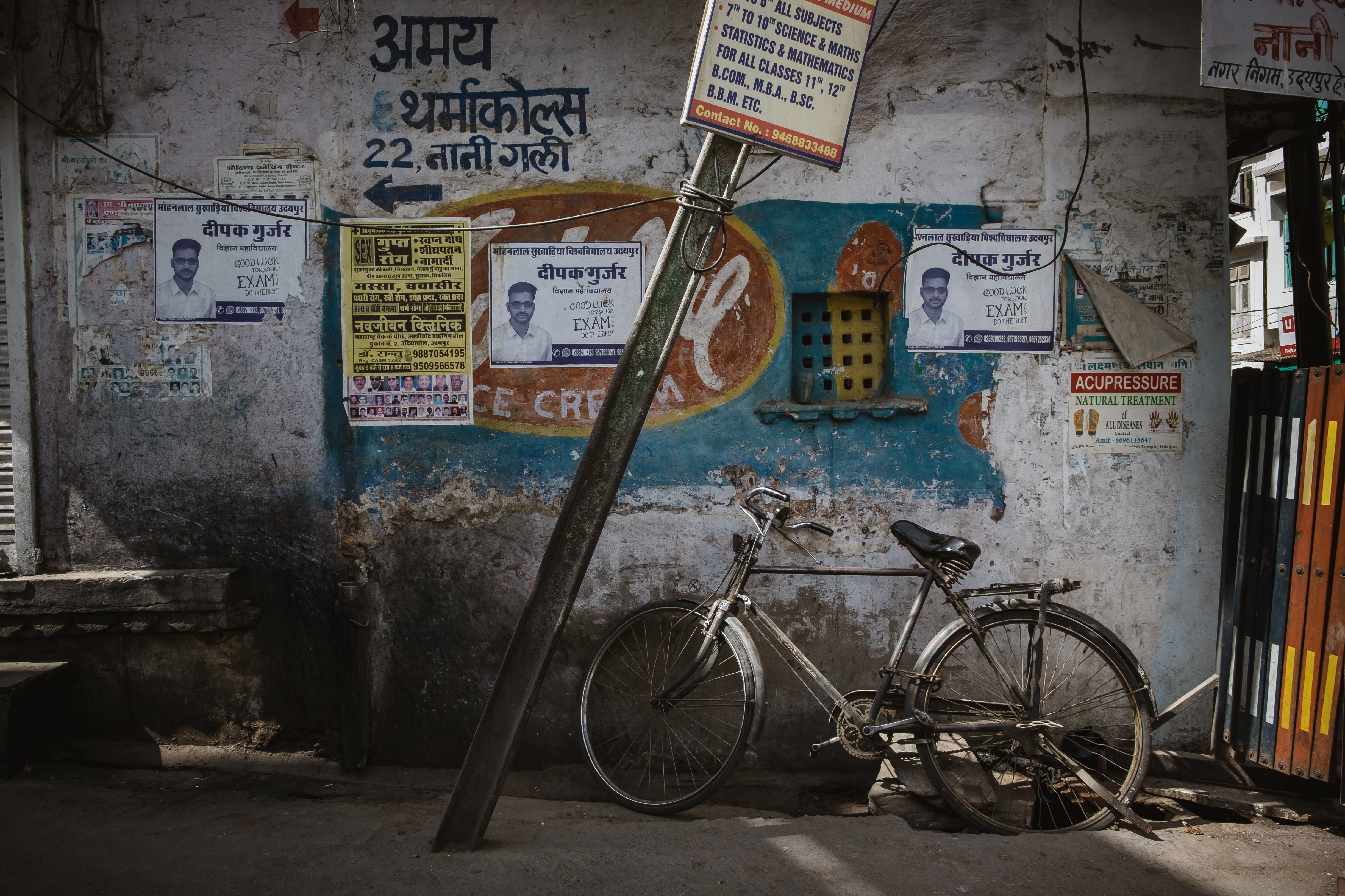 gray steel bicycle leaning on gray wall