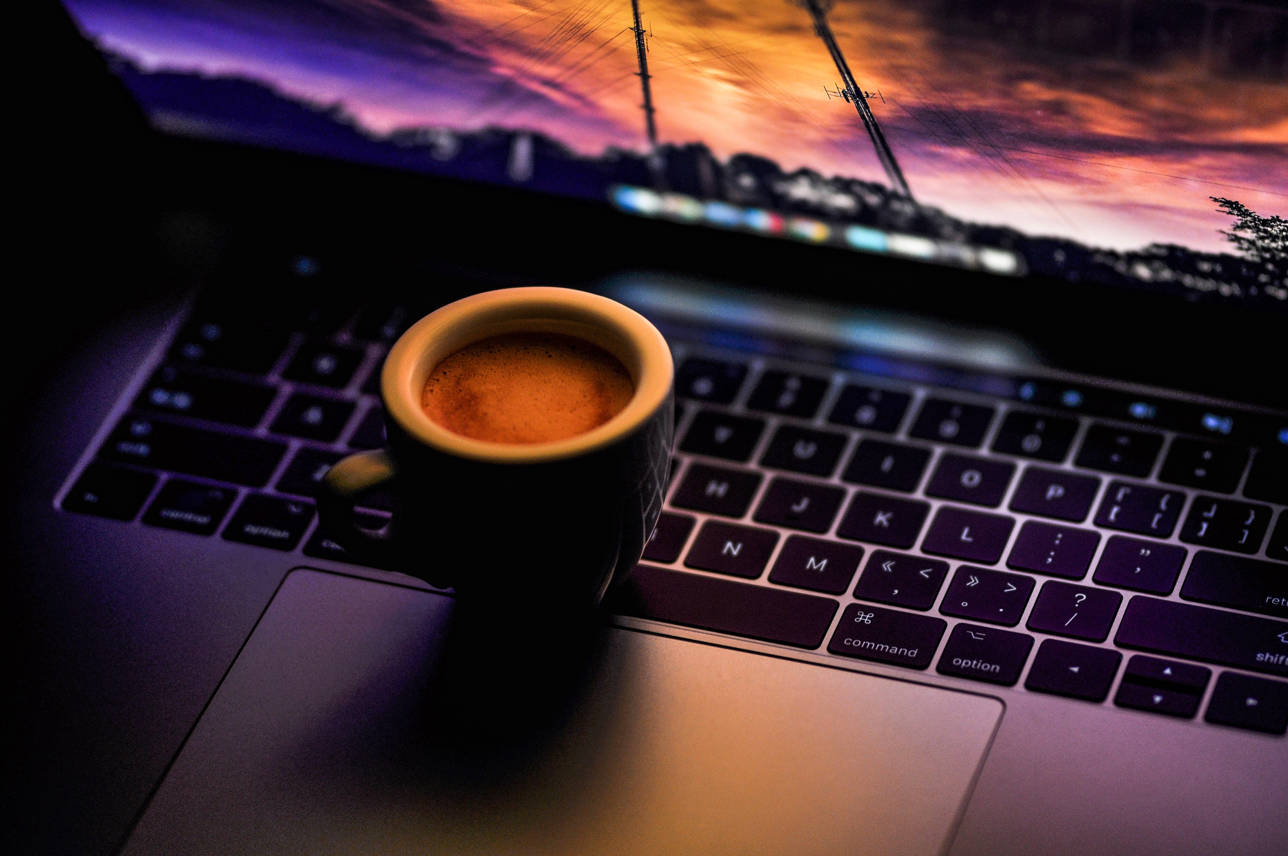 black ceramic coffee mug on MacBook Pro