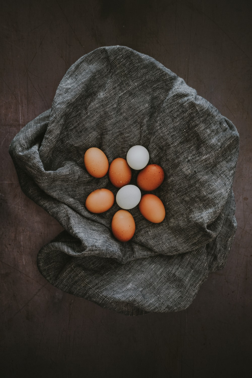 white and brown egg lot on grey textile
