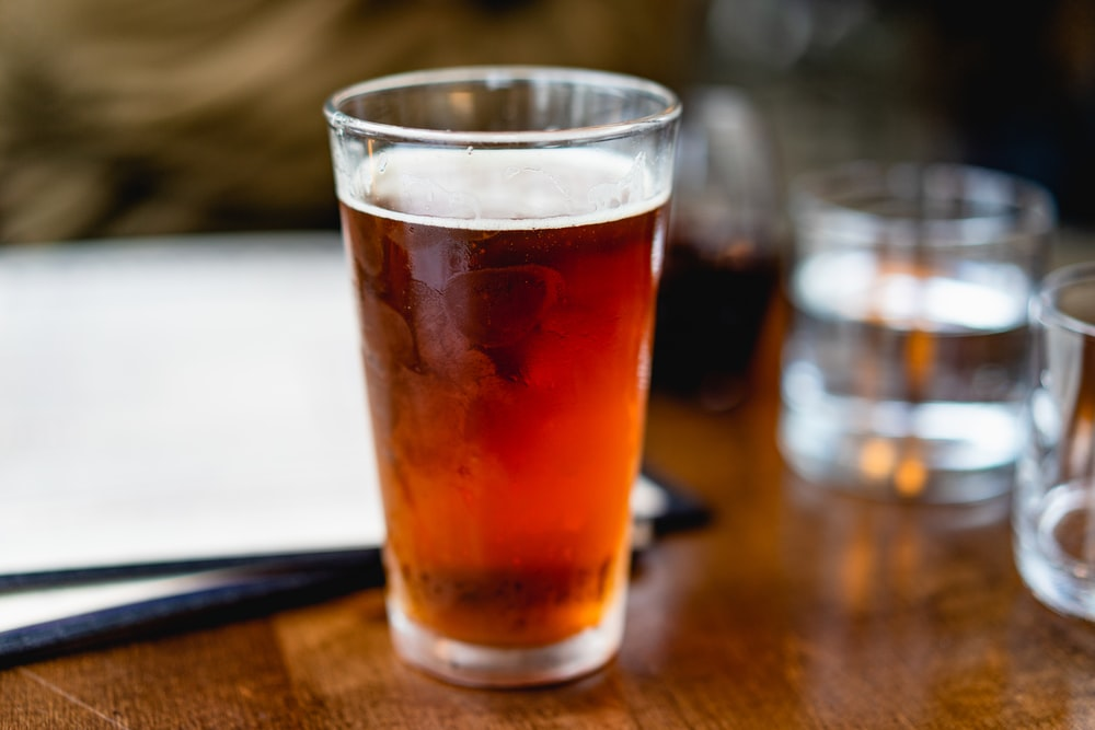 beverage filled clear pint glass on top of brown surface