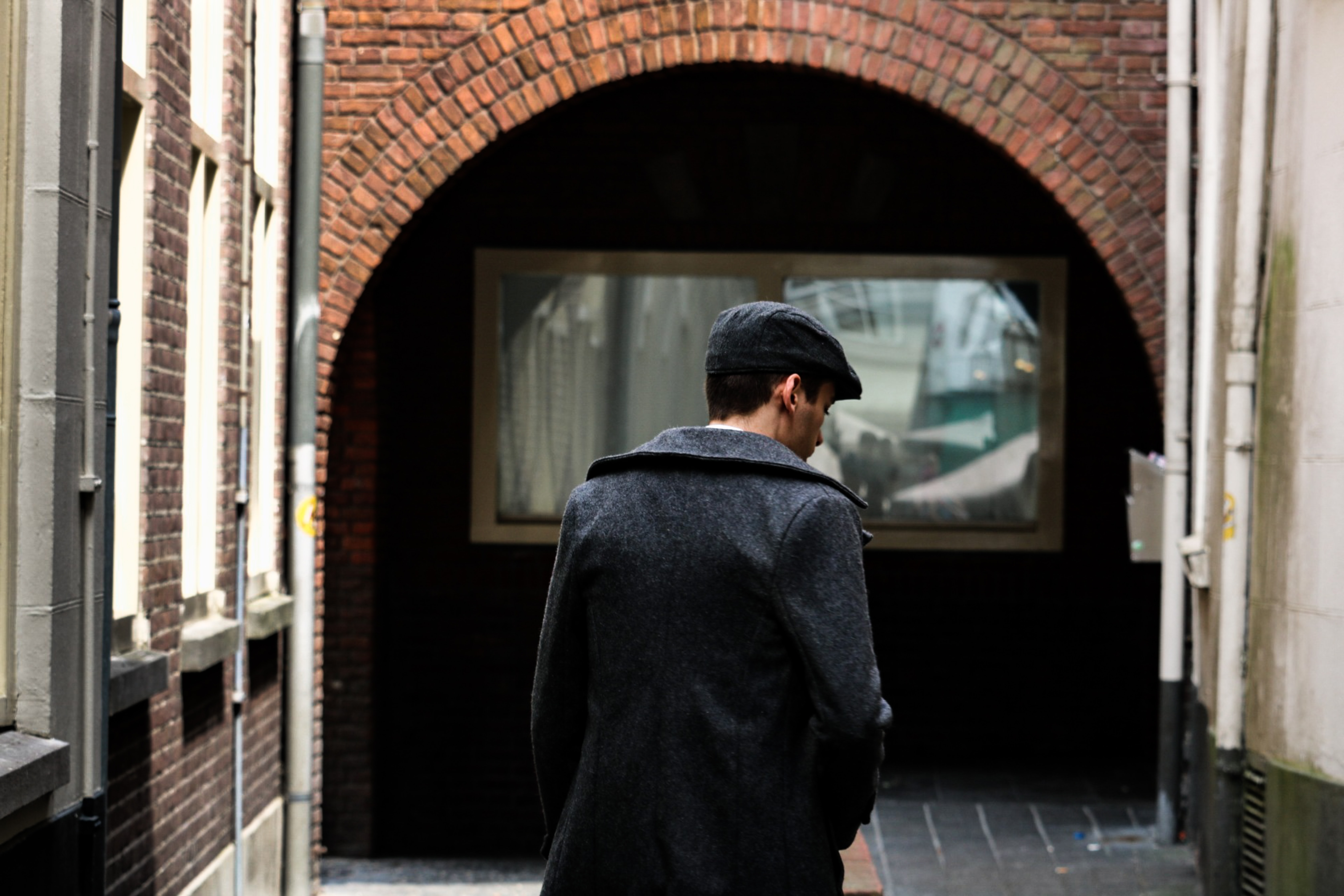 person walking on street near white building