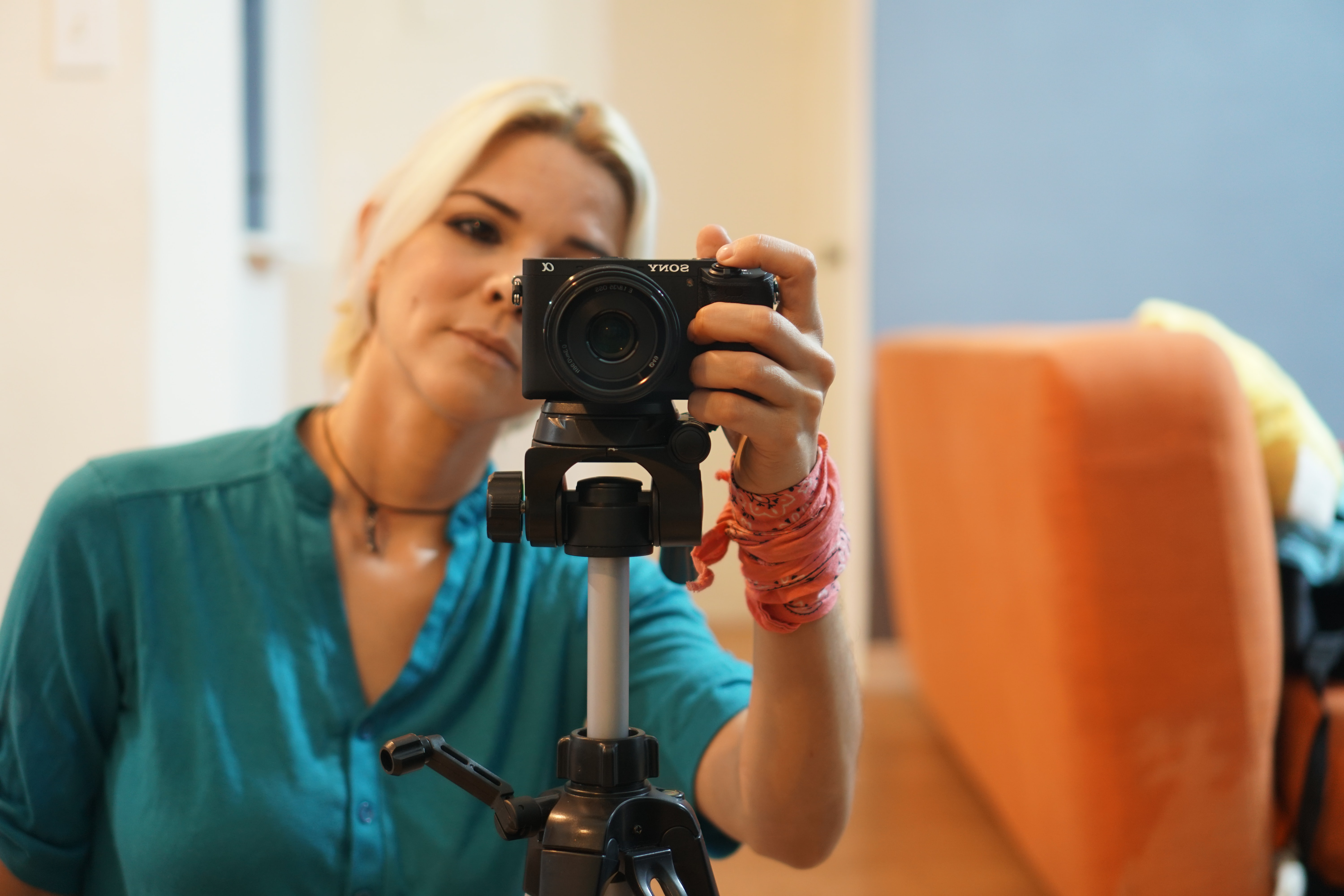 woman in blue dress holding the camera