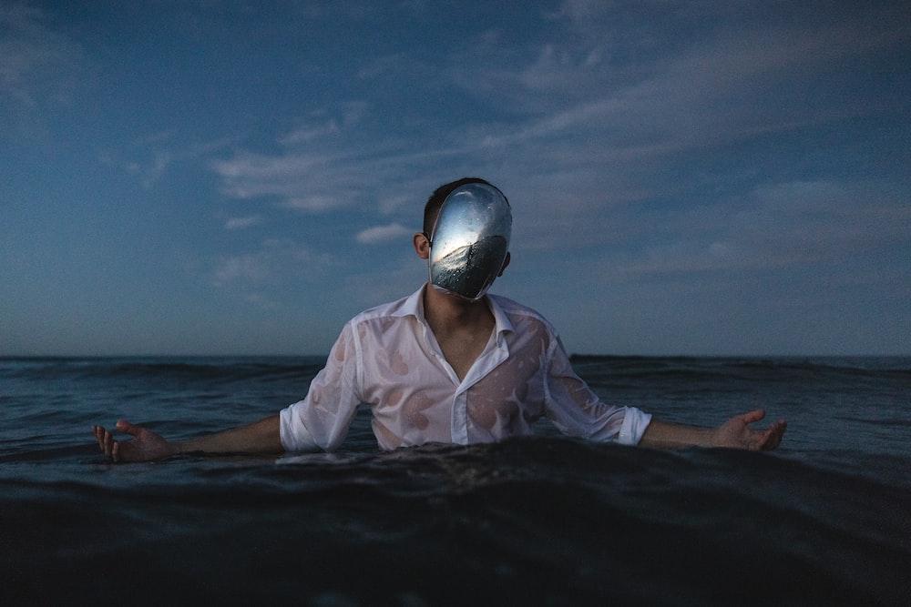 man wearing white dress shirt standing on body of water