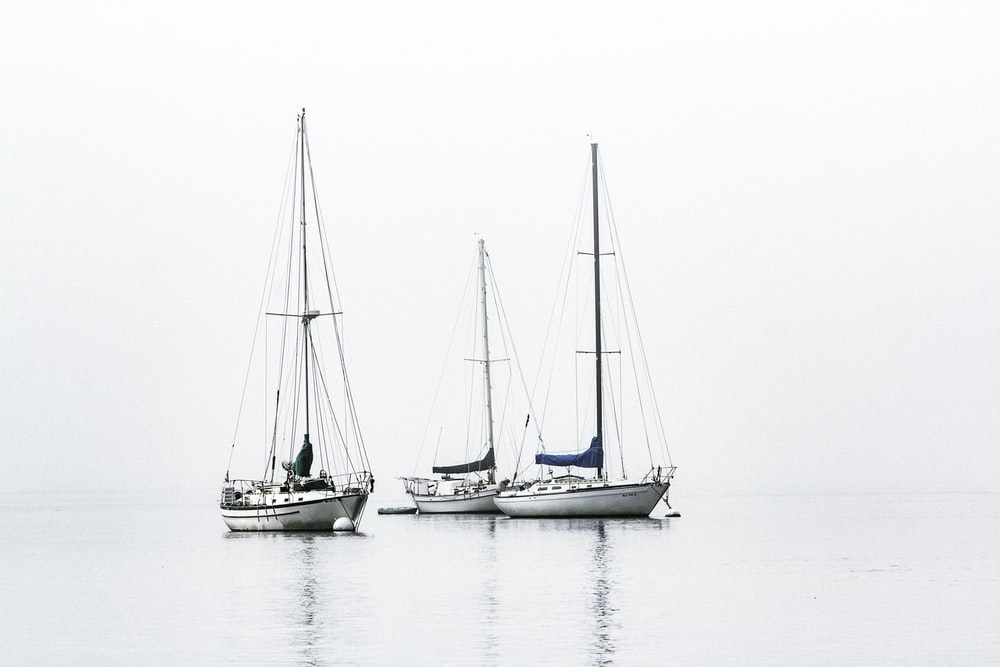 three white boats on sea during daytime