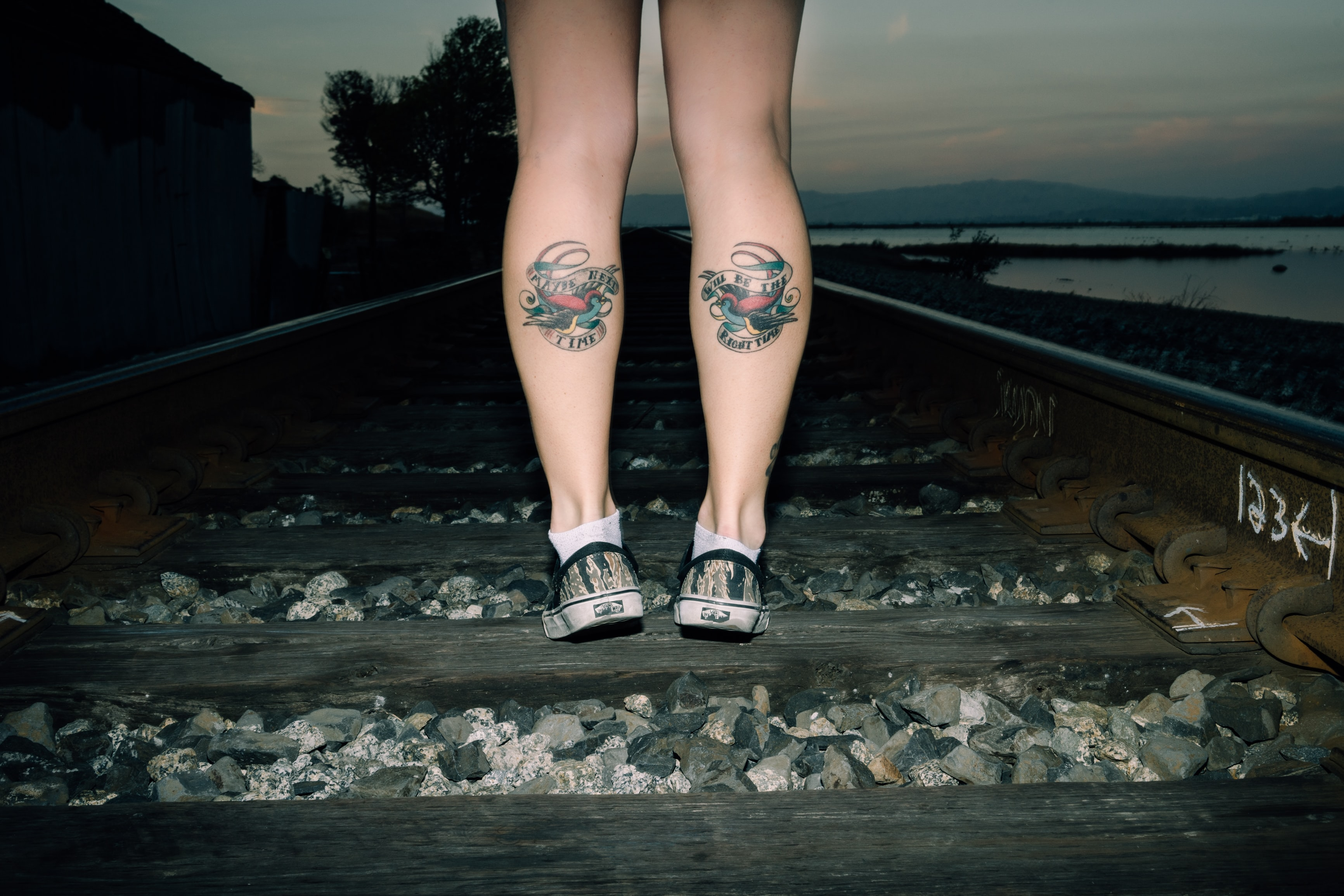 person standing on railroad with foot tattoo
