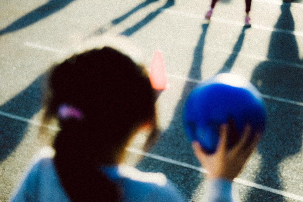 girl holding blue ball
