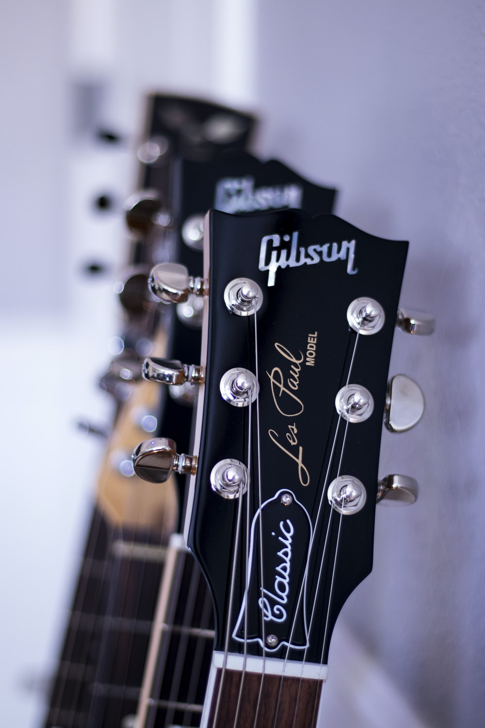 shallow focus photography black Gibson guitar headstock