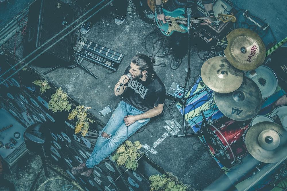 man sitting while singing beside instruments