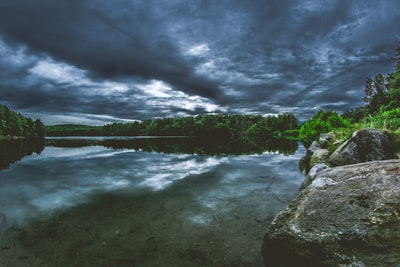 body of water surrounded by trees under cloudy sky moody teams background