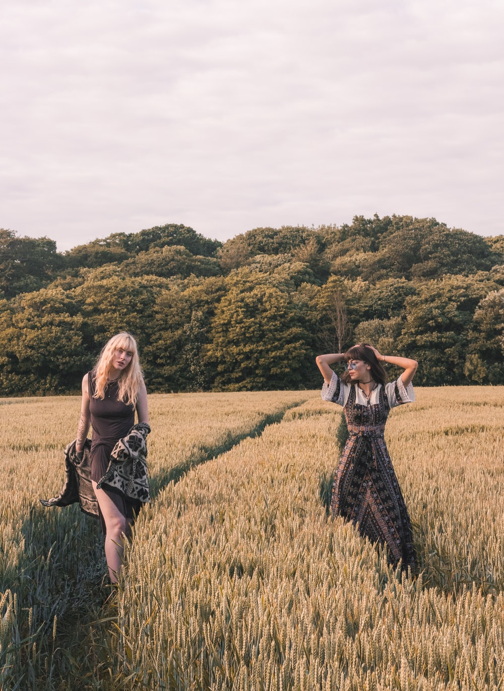 two women walking on wheat field during daytime