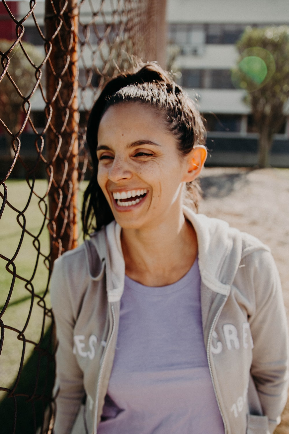 smiling woman wearing gray zip-up pullover hoodie standing near brown metal chain link fence during daytime