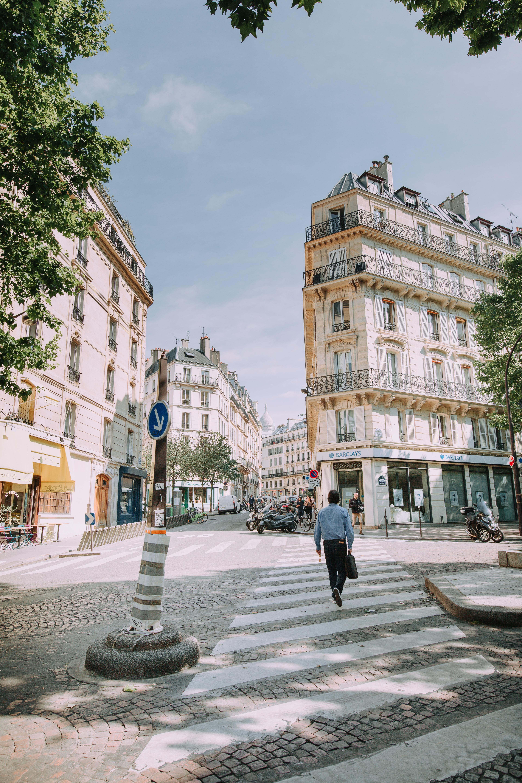 man walking on pedestrian lane near concrete building at daytime
