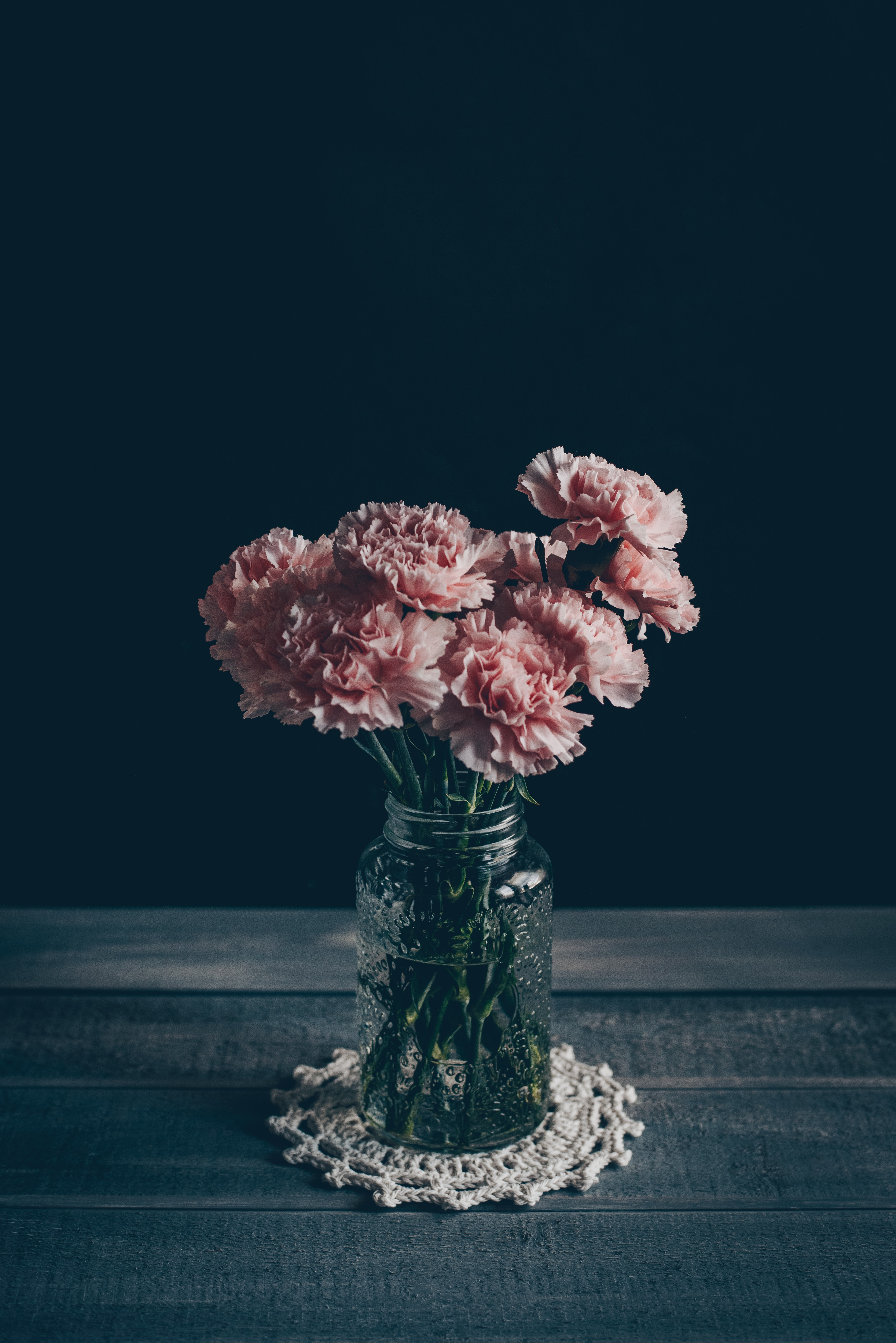 pink petaled flower centerpiece on gray wooden table