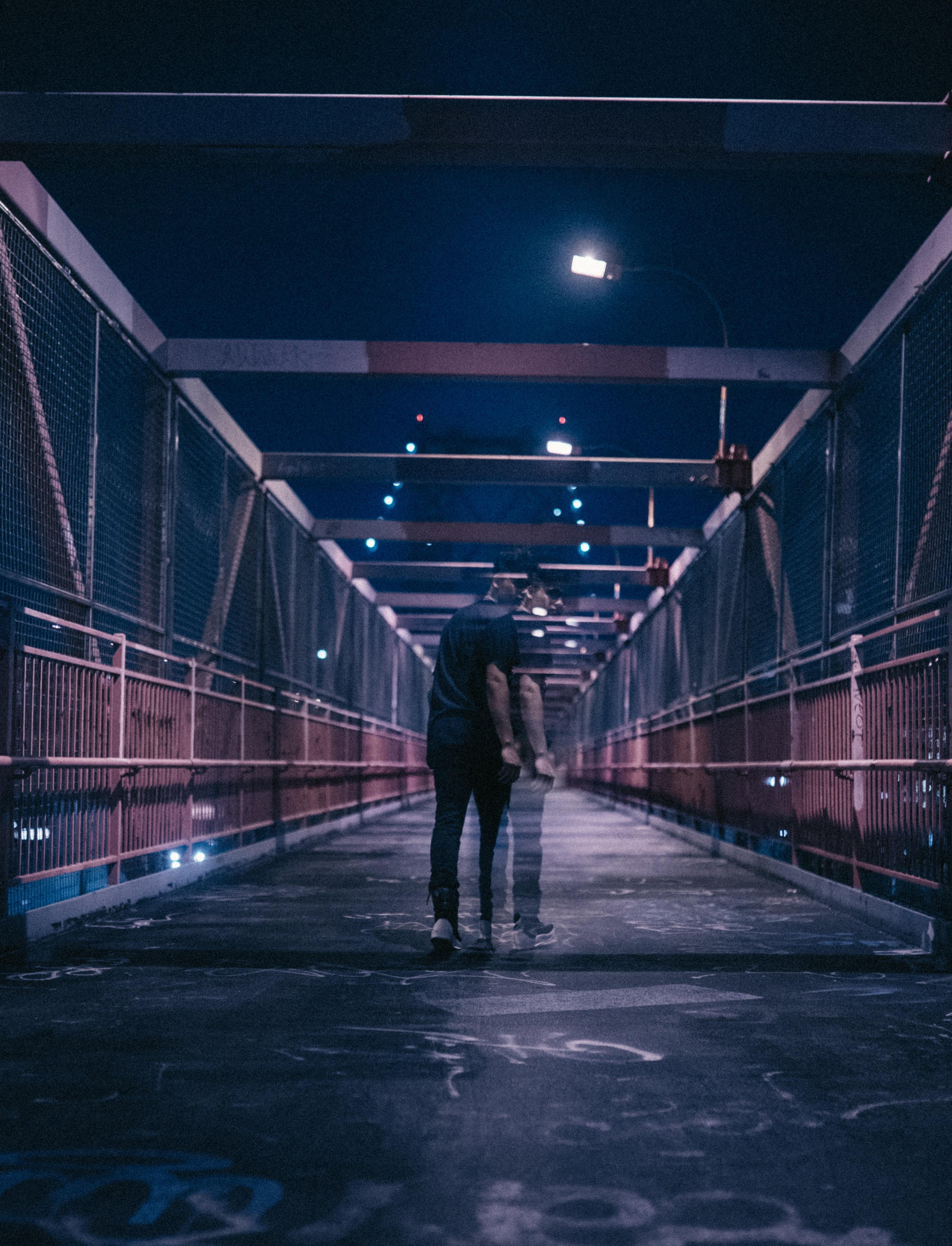 man walking on bridge during nighttime