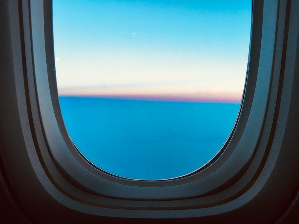 airplane window showing blue sky