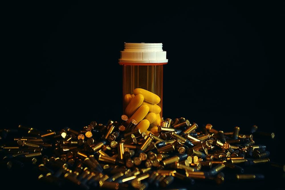 white medication pill in orange prescription bottle