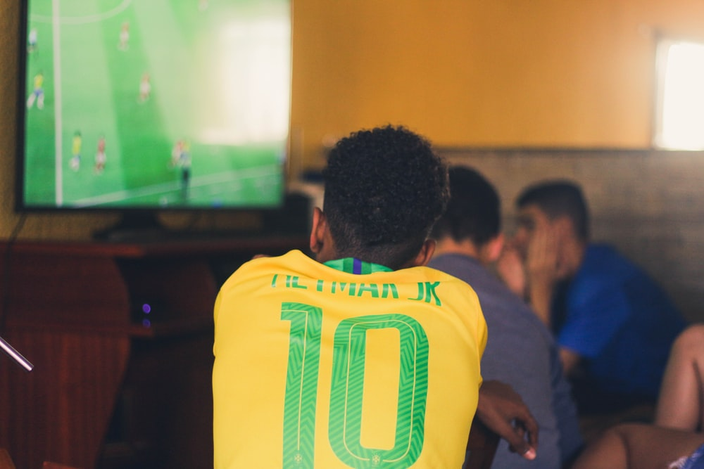 man wears yellow and green jersey shirt