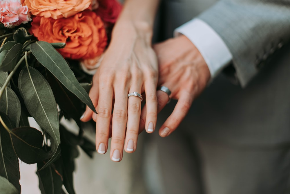 couple wearing silver-colored rings