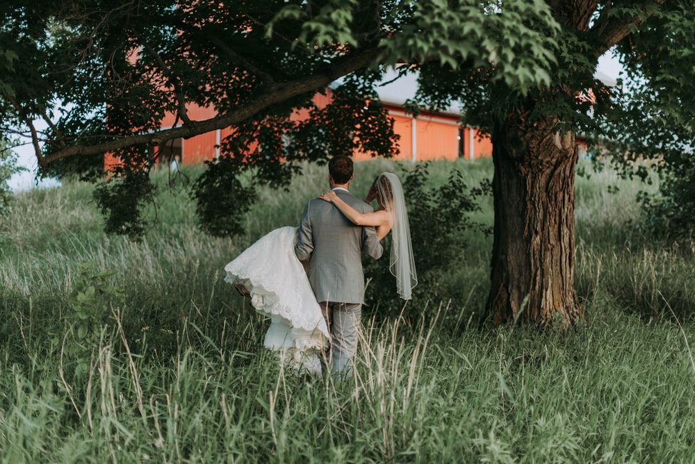 husband carrying his wife walking beside trees