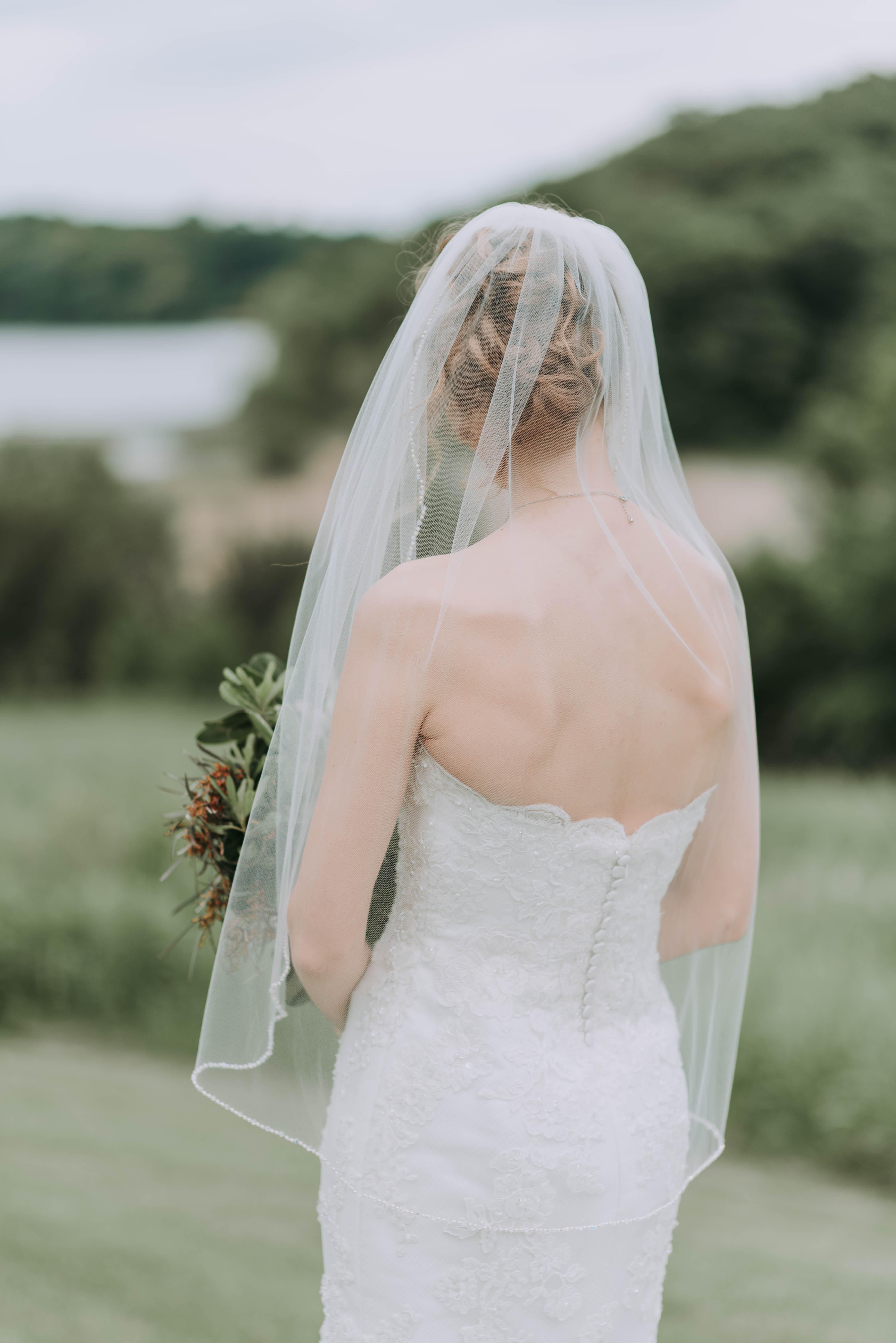 woman wearing white wedding dress holding bouquet
