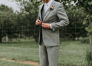 standing man holding his notched lapel suit jacket's button