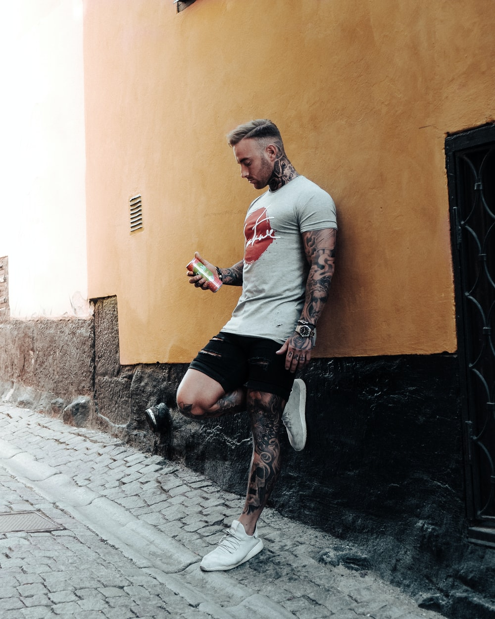 man covered with tattoo leaning on wall holding can during daytime