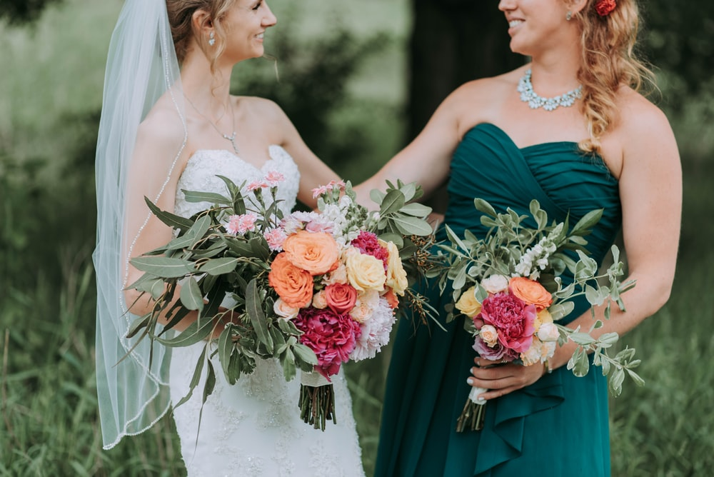 bride holding bouquet of assorted-color flowers standing on grass field