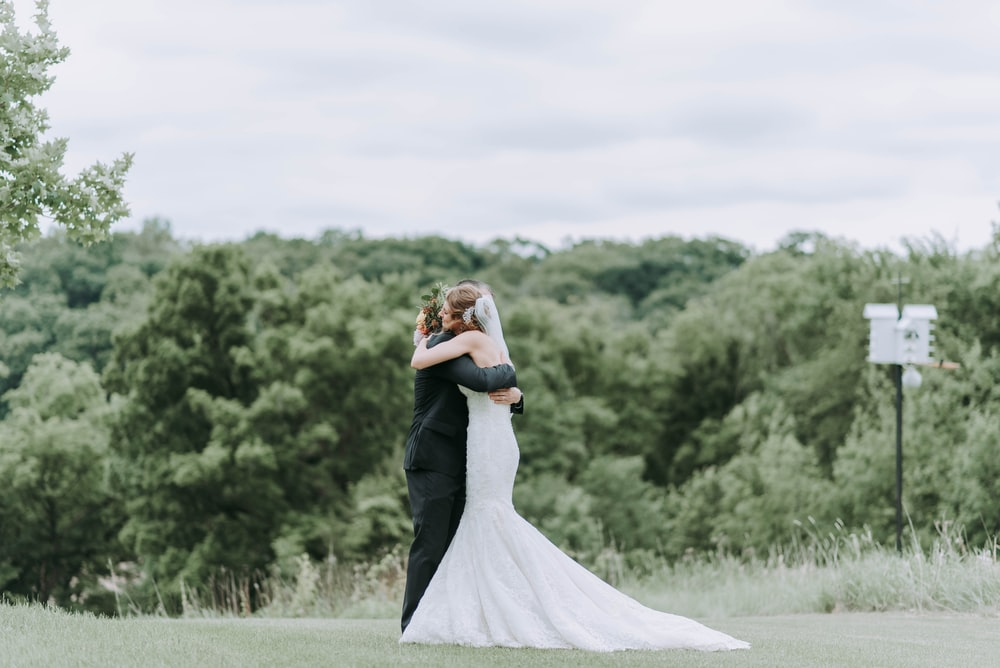 woman hugging man standing on green grass field