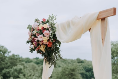bouquet of assorted-color flowers hanged on brown plank with white textile wedding teams background