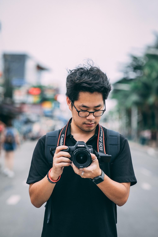 man holding black Canon EOS DSLR camera