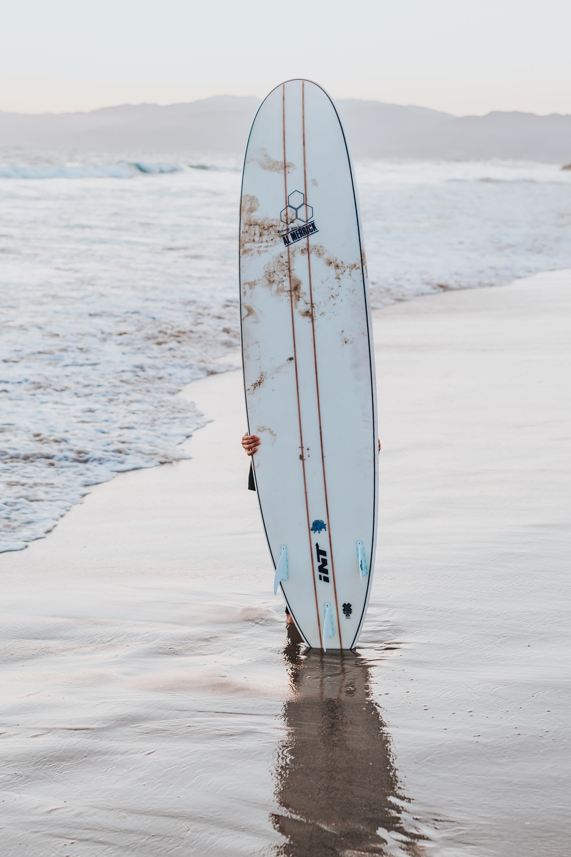 white surfboard upright on seashore during daytime