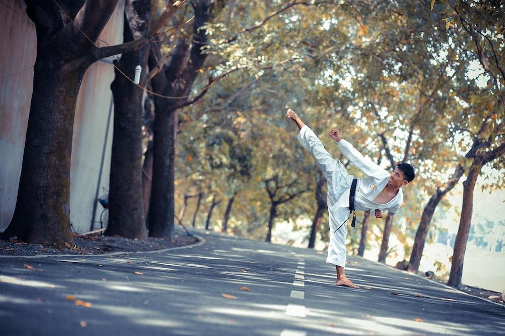 man wearing karate gi standing on road