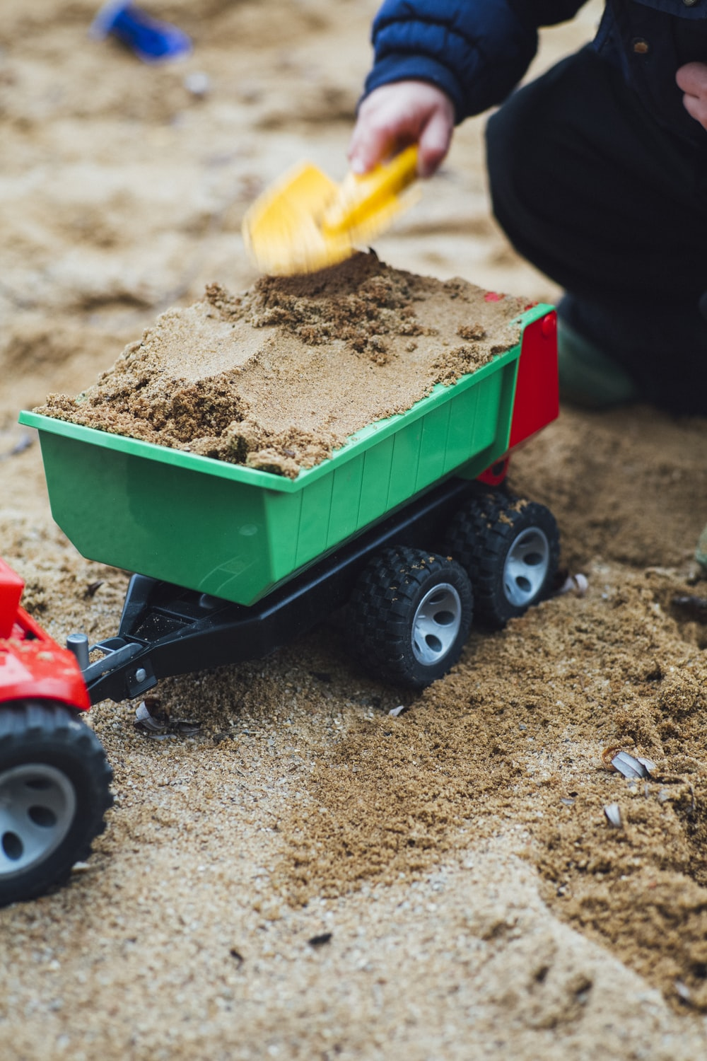 selective focus photo of toy trailer filled of brown sands