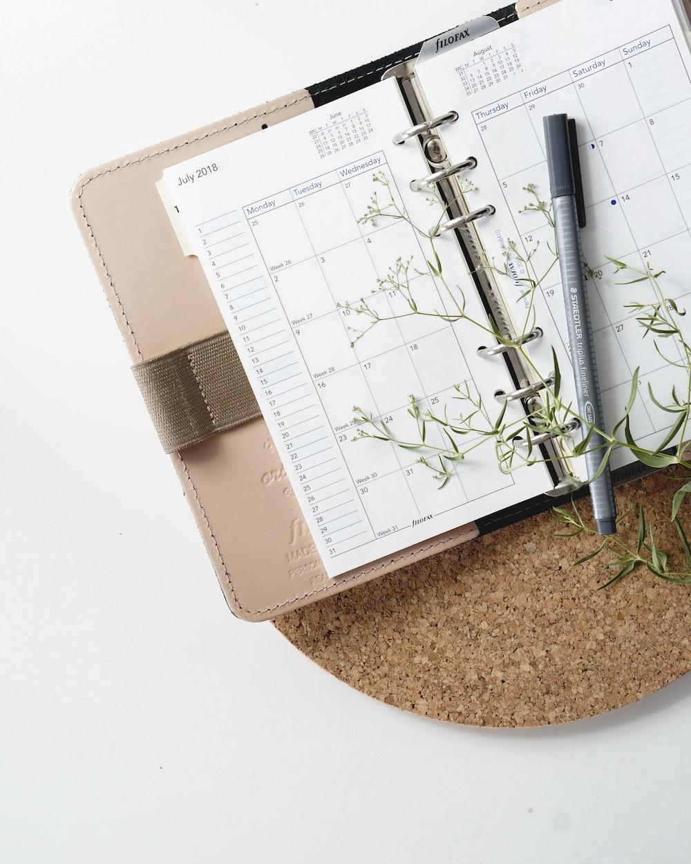 grey and black pen on calendar book