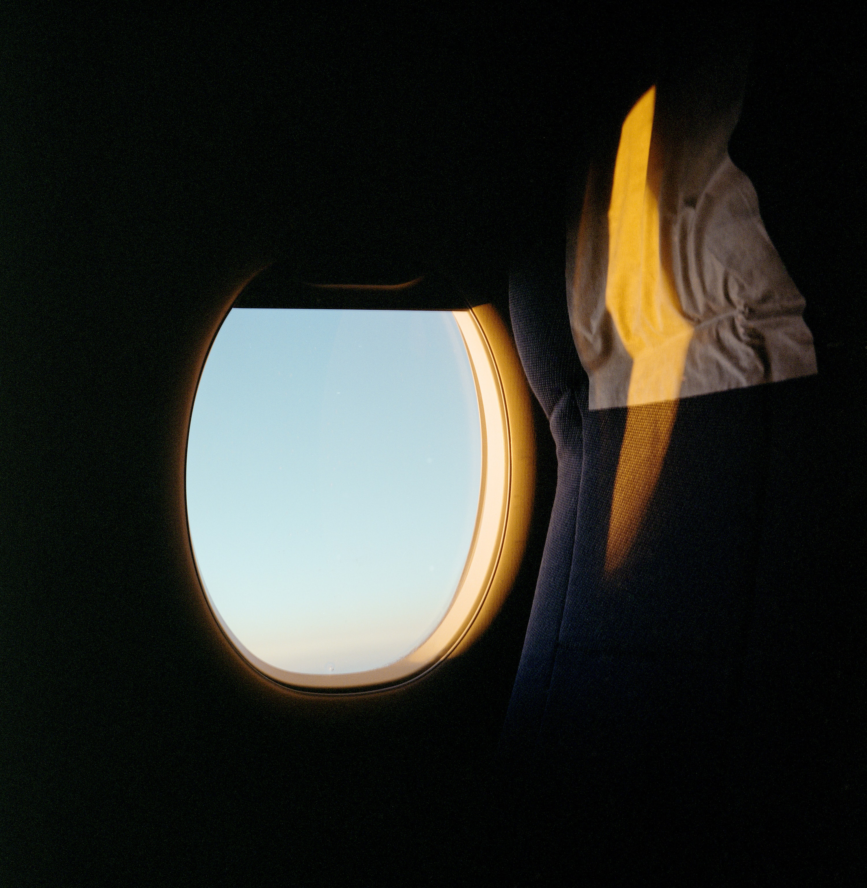 person taking photo of blue sky inside airplane