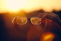 focus photo of person holding black framed eyeglasses