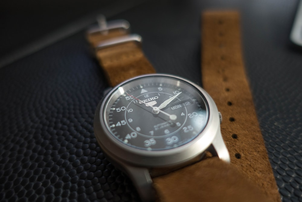 round silver-colored analog watch with brown leather band