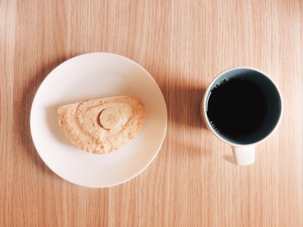 mug full of black coffee near a slice of cake